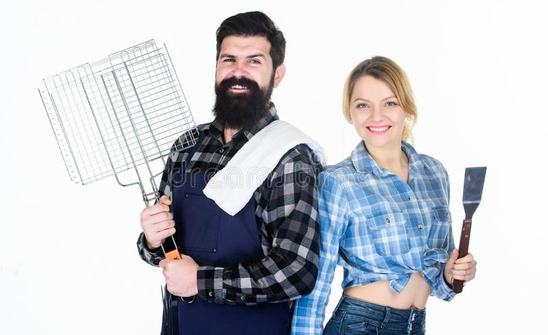 Barbecuing to perfection. Tools for roasting meat. Family weekend. Man bearded hipster and girl. Preparation and stock image
