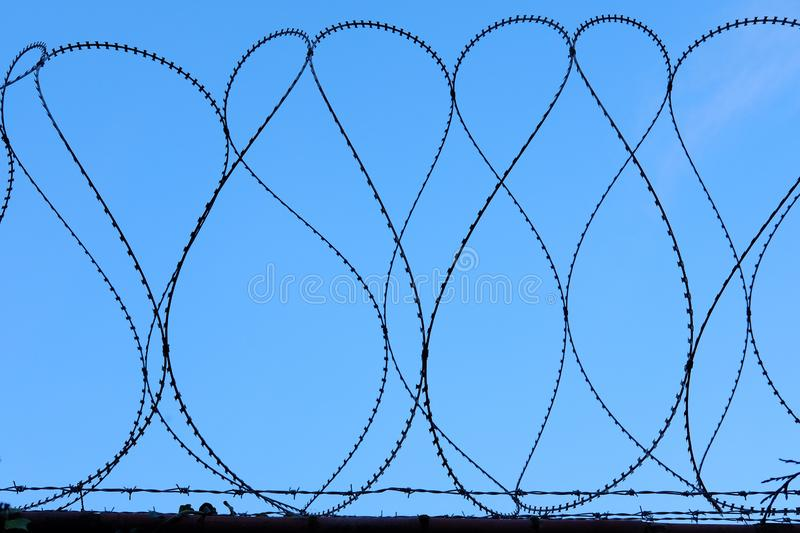 Barbed Razor Wire Military Security Fence Against Blue Sky stock photo