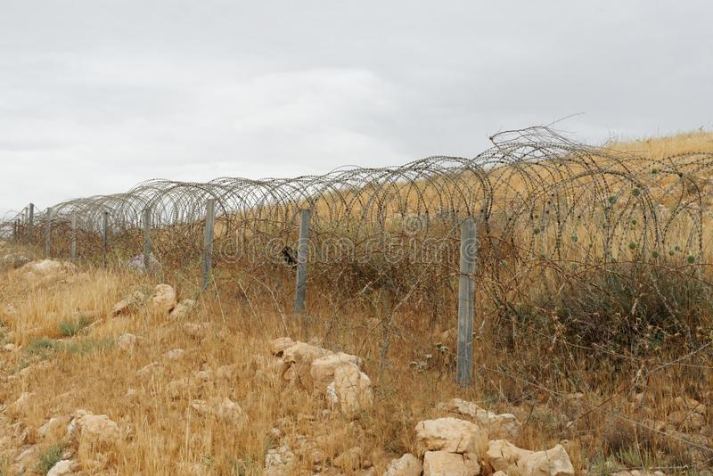 Barbed tape or razor wire fence across the desert hill on cloudy day stock photography