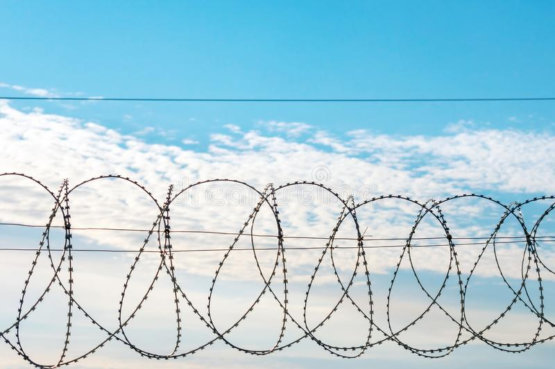 Barbed wire against a blue sky. With feathery clouds. There`s room for your text stock image