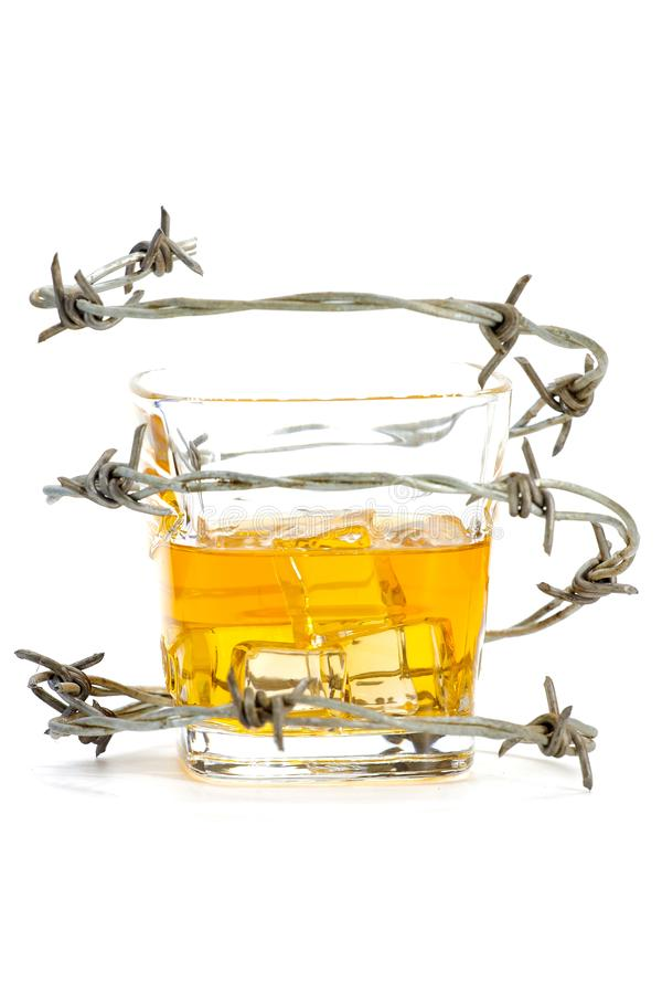 Barbed wire around glass with ice and alcohol royalty free stock photo