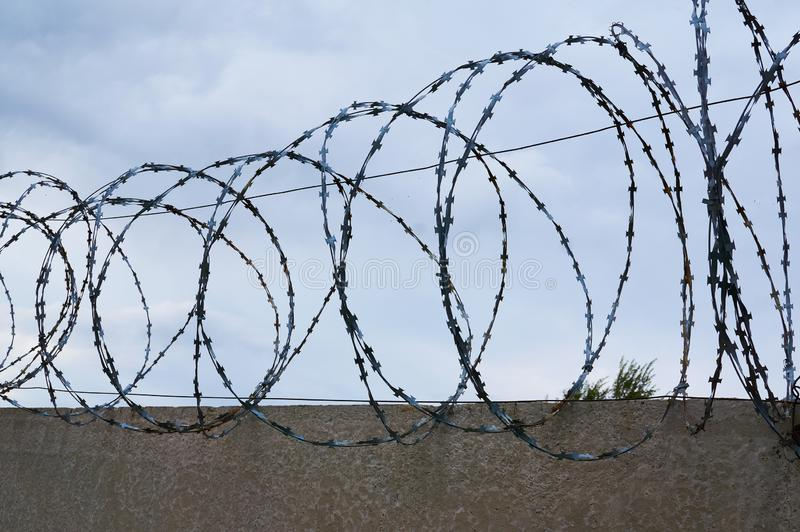 Barbed wire on the background of a concrete fence and a cloudy sky. royalty free stock images