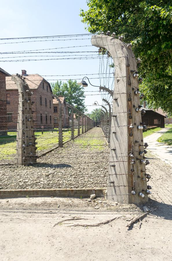 Auschwitz-Birkenau, concentration camp, Poland. Barbed wire electrical fences and barracks of the former nazi extermination camp of Auschwitz-Birkenau in royalty free stock image