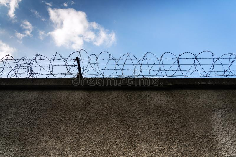 Barbed wire fence around prison walls, blue cloudy sky in background, security, crime illegal immigration concept stock photo