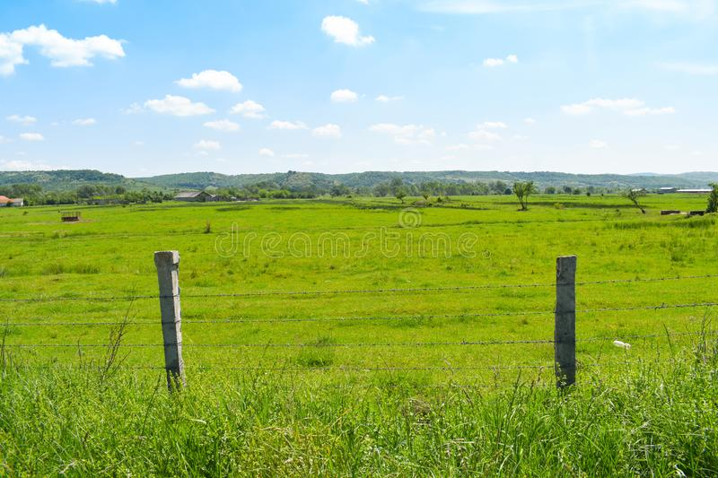 Barbed wire fence in the beautiful green valley in a sunny summer day with bright blue sky and white clouds royalty free stock image
