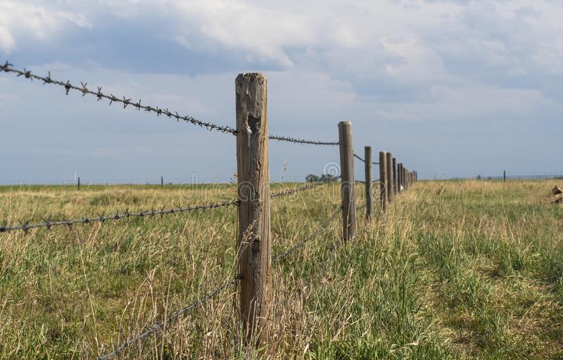 Barbed wire fence with blue cloudy skies bordering farm property in the prairies wild grass of alberta royalty free stock photo