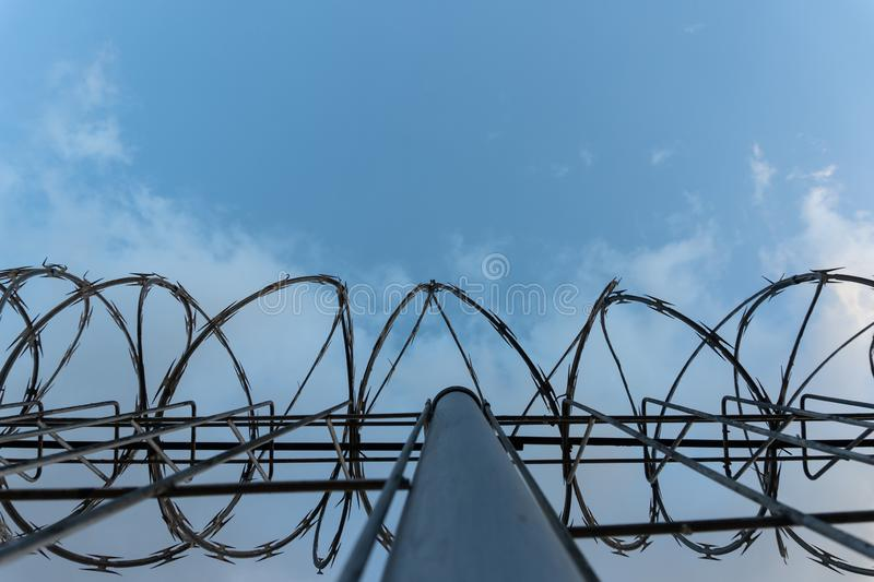 Barbed wire fence with bright blue sky to feel silent and lonely and want freedom. Dramatic clouds behind barbed wire fence on a. Prison wall. Fence around stock photography
