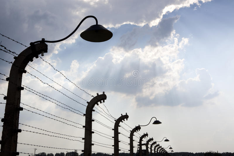 Barbed wire fence in impressive sky. Auschwitz royalty free stock images