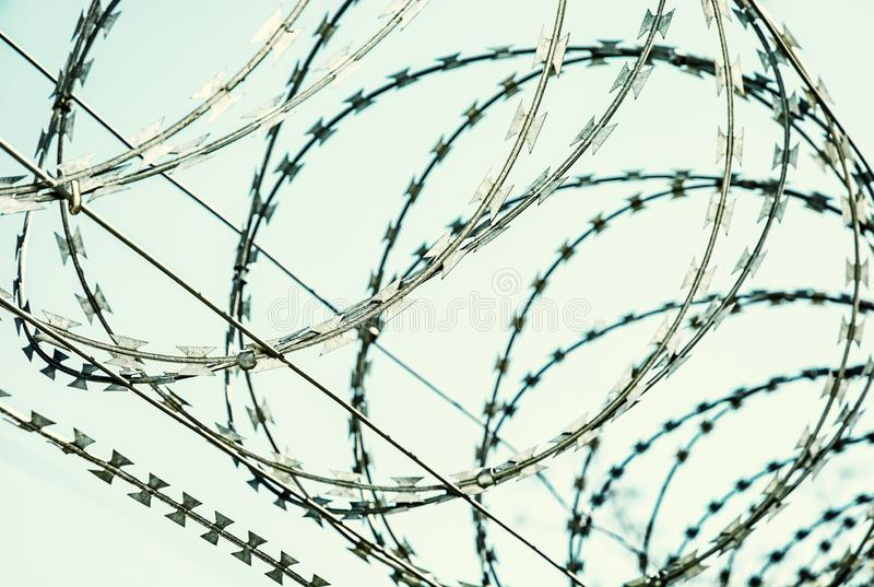 Barbed wire fence for protection. Entry ban. Cold photo filter royalty free stock image