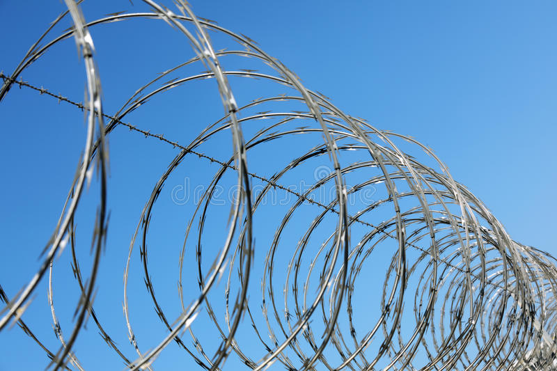 Barbed wire fence. Razor and barbed wire fence concept for security and protection stock images