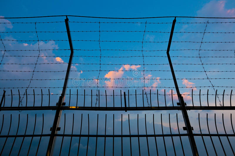 Barbed wire fence silhouettes against cloudy dark blue sky at sunset stock photos