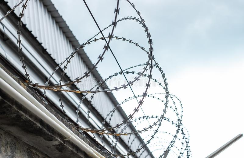 Barbed wire fences installed on the wall to protect the area stock image