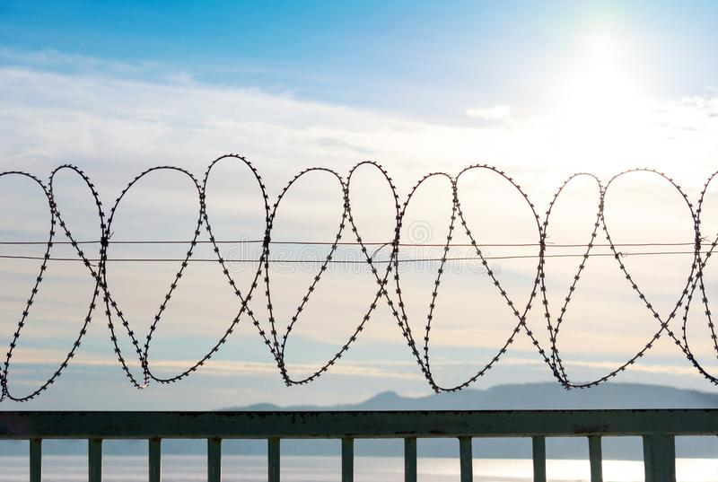 Barbed wire on a metal fence. Behind the fence is a blue sky with feathery clouds. In the lower part you can see of the mountains and river. Back light from royalty free stock images