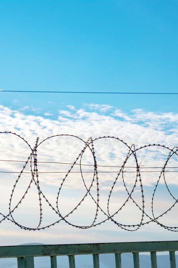 Barbed wire on a metal fence. Behind the fence is a blue sky with feathery clouds. Vertical photography royalty free stock image