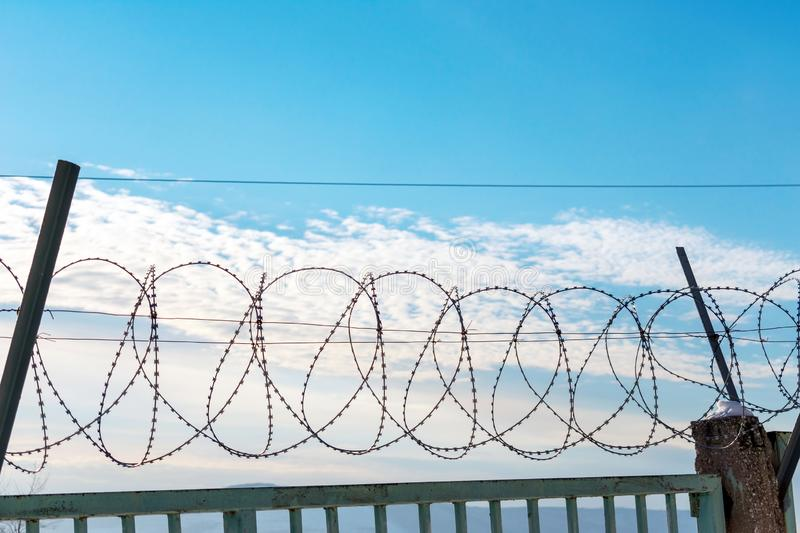 Barbed wire on a metal fence. Behind the fence is a blue sky with feathery clouds. You can see the pillars on which is attached Spiral Bruno royalty free stock photos