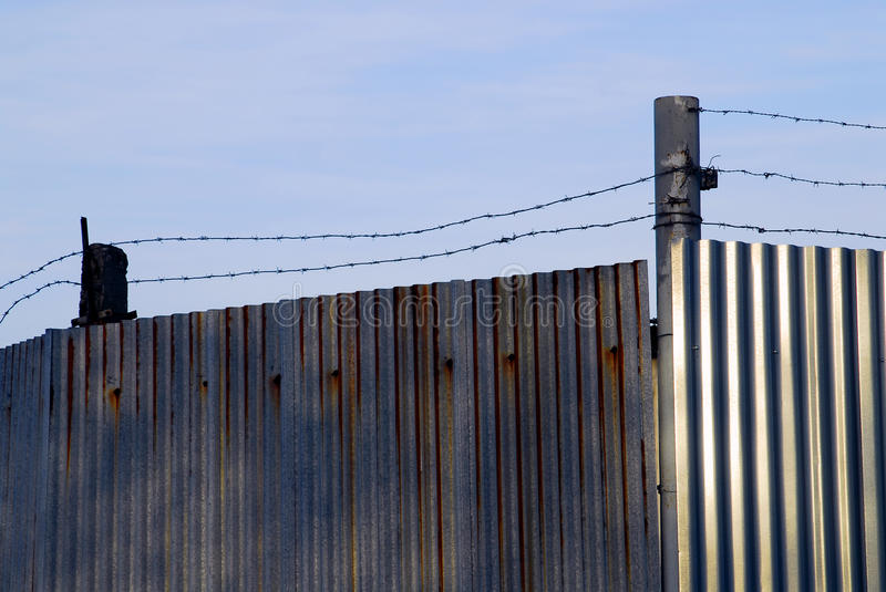 Barbed wire on the metal wall stock image