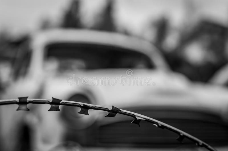 A barbed wire for protection no trespassing not allowed background. Vintage car in background royalty free stock photos