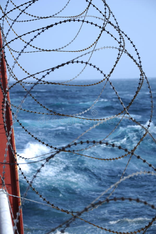 Barbed wire by rough sea