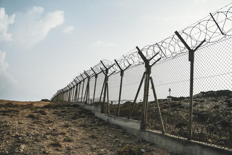 barbed wire steel wall against the immigations. Wall with barbed wire on the border of 2 countries. Private or closed military stock photography