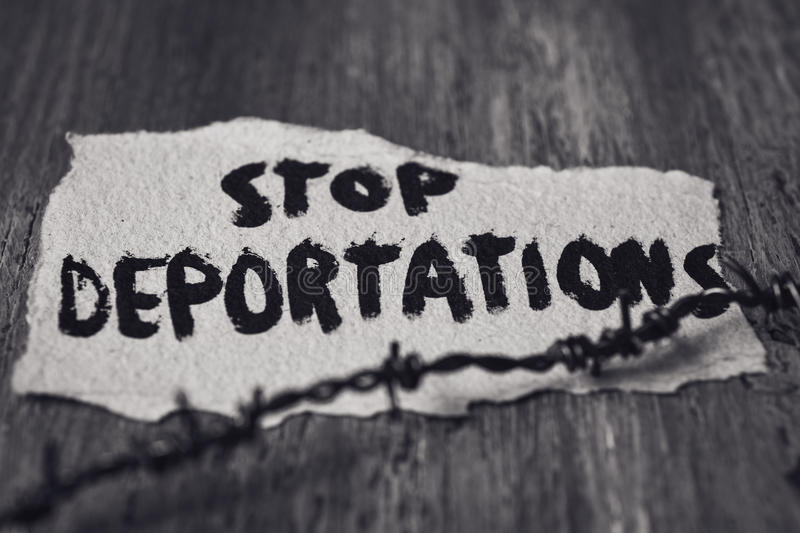 Barbed wire and text stop deportations. Closeup of a barbed wire and a piece of paper with the text stop deportations handwritten in it on a rustic wooden stock images