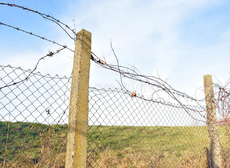 The barbed wire in two rows as protection against unauthorized entry into private territory. The detail fence with barbed wire in two rows as protection against royalty free stock images