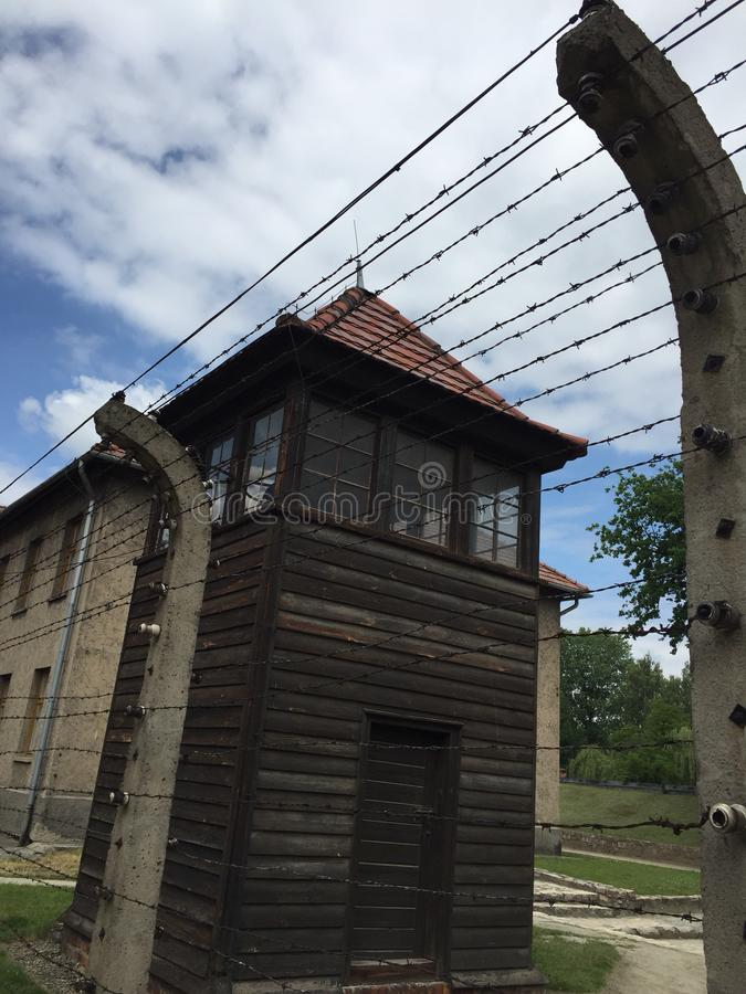 Auschwitz concentration camp guard tower and barbed wire fence royalty free stock photos