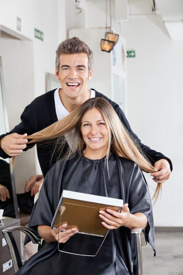 Barbeiro com o cliente que guarda o espelho no salão de beleza fotografia de stock