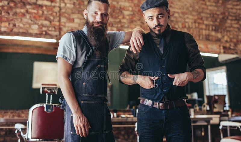 Barbeiro com o homem novo à moda que está no salão de beleza fotos de stock royalty free