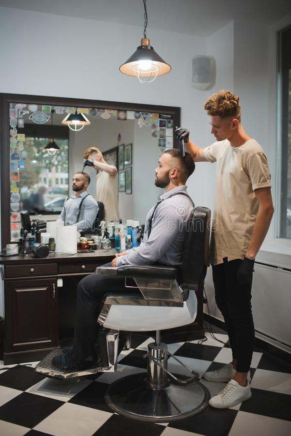 Barbeiro com uma escova de cabelo que trabalha em um corte de cabelo novo para um cliente Cliente farpado no fundo do barbeiro Co fotografia de stock royalty free