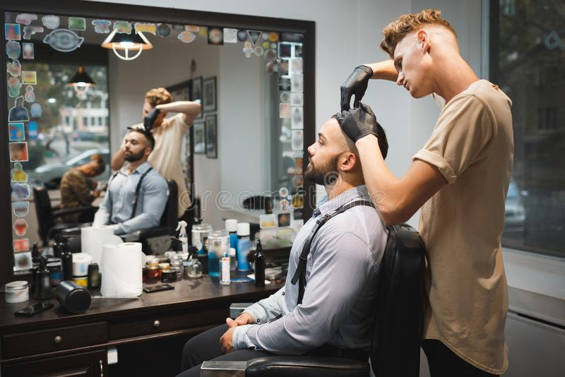 Barbeiro com uma escova de cabelo que trabalha em um corte de cabelo novo para um cliente Cliente farpado no fundo do barbeiro Co foto de stock