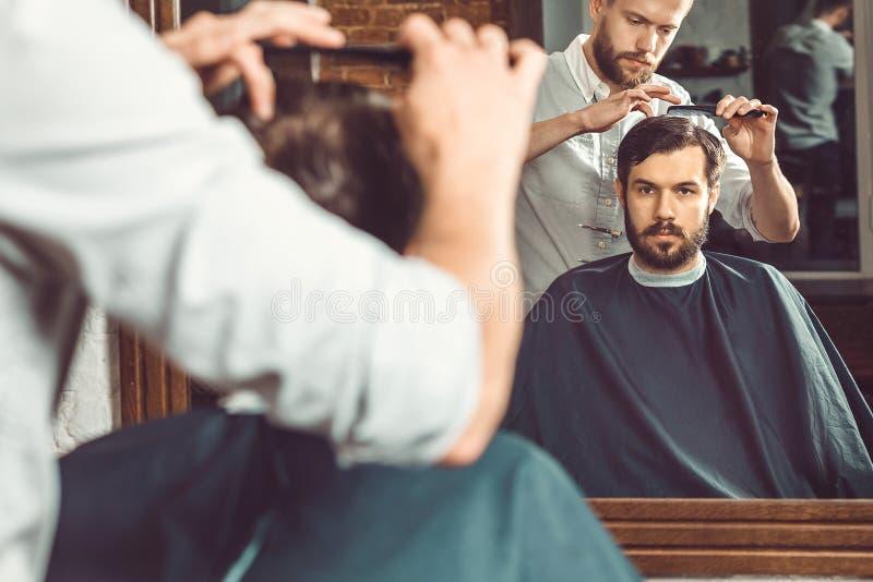 Barbeiro considerável novo que faz o corte de cabelo do homem atrativo no barbeiro imagem de stock