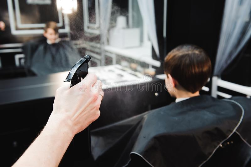 Barbeiro considerável novo que faz o corte de cabelo do menino bonito no barbeiro fotos de stock royalty free