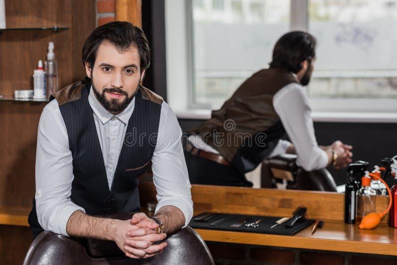 barbeiro considerável que inclina-se na cadeira no local de trabalho e na vista fotos de stock