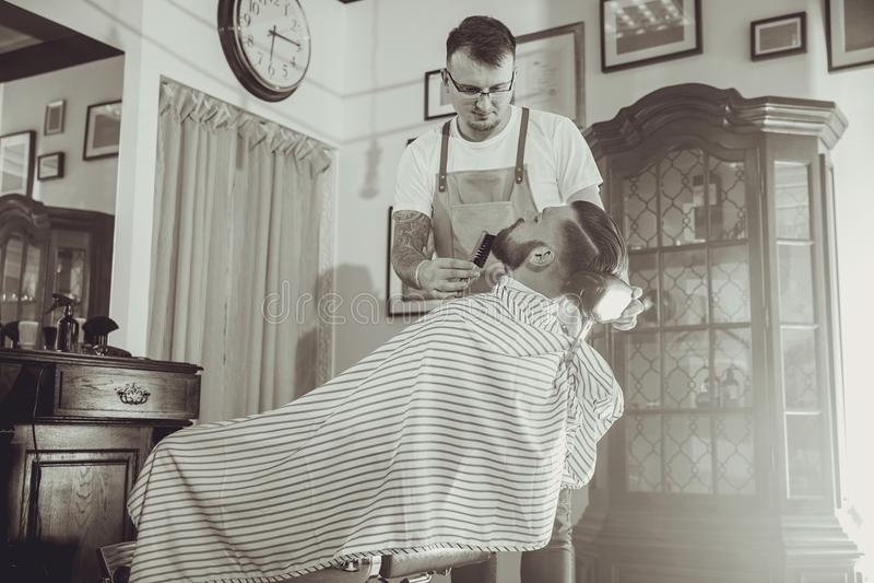 Barbeiro durante o trabalho em sua barbearia imagem de stock royalty free