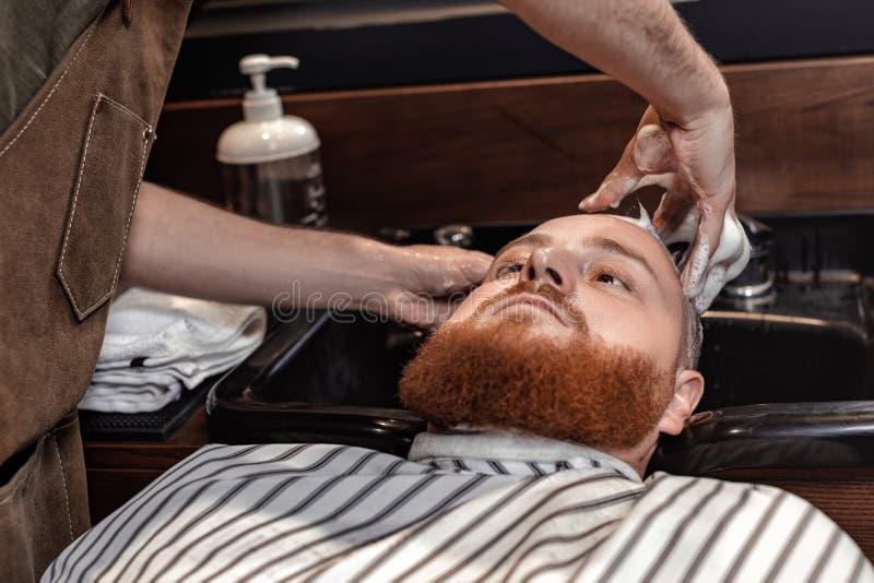 Barbeiro e homem farpado na barbearia fotos de stock