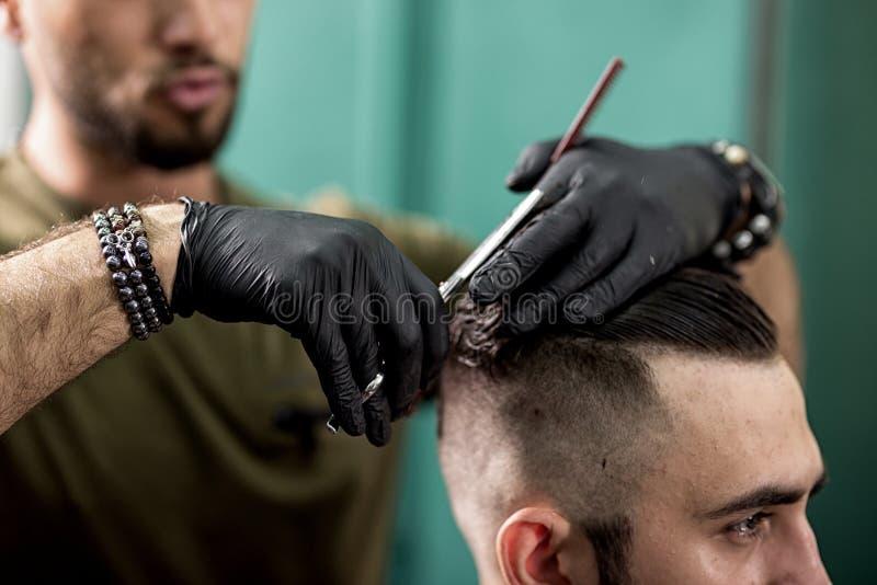 Barbeiro em cortes pretos das luvas com cabelo das tesouras do homem à moda em um barbeiro imagens de stock royalty free