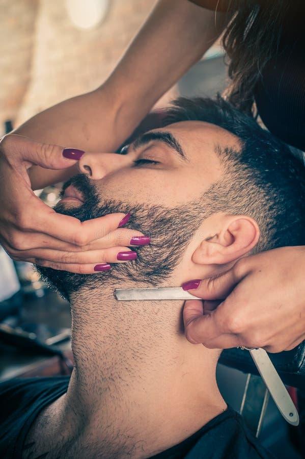 Barbeiro fêmea que barbeia um cliente foto de stock