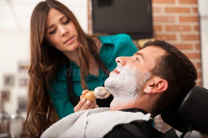 Barbeiro fêmea que barbeia um homem foto de stock