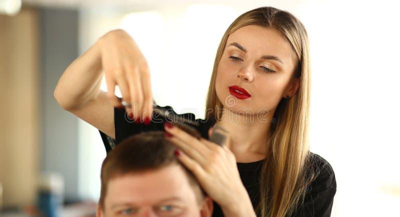 Barbeiro fêmea que corta o cabelo do cliente do homem imagem de stock royalty free