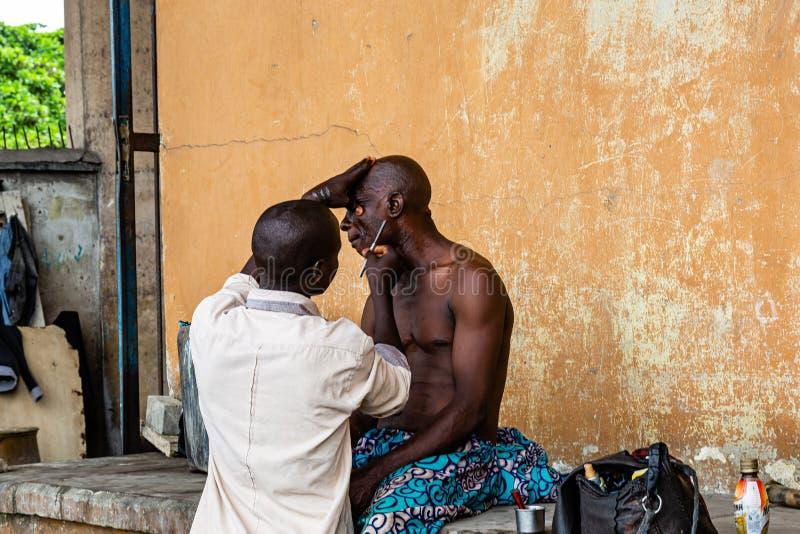 Barbeiro incipiente sob as pontes de Marina Lagos Nigéria África Ocidental foto de stock