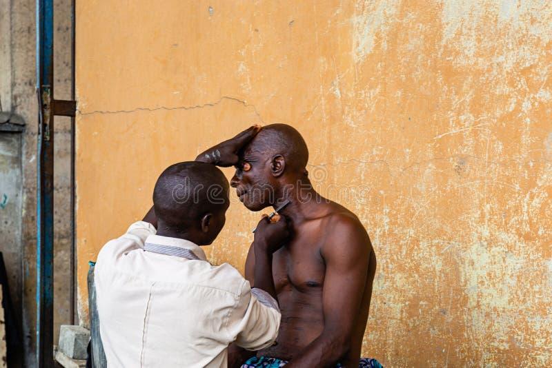 Barbeiro incipiente sob as pontes de Marina Lagos Nigéria África Ocidental imagem de stock