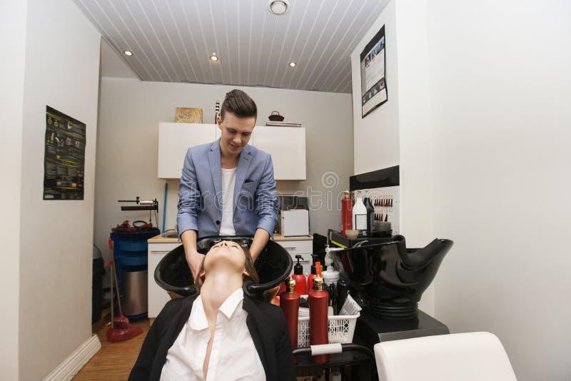 Barbeiro masculino que lava o cabelo do cliente fêmea no salão de beleza foto de stock royalty free