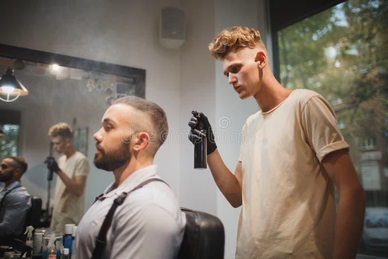 Barbeiro novo com um pulverizador de cabelo que trabalha em um fundo borrado Cliente à moda no conceito da ocupação do barbeiro d fotos de stock