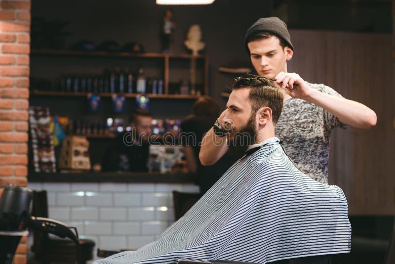 Barbeiro novo que faz o corte de cabelo do homem farpado no barbeiro imagens de stock royalty free