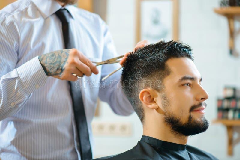 Barbeiro profissional que faz o corte de cabelo fotos de stock