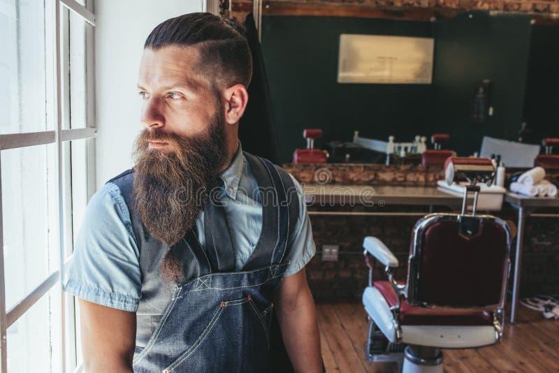 Barbeiro que está pela janela e que olha afastado imagens de stock royalty free