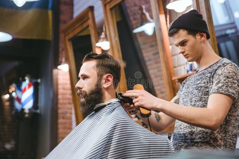 Barbeiro que faz o corte de cabelo ao homem considerável com barba foto de stock
