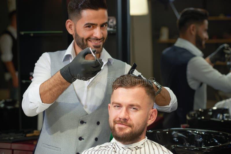 Barbeiro que faz o corte de cabelo na moda ao homem novo na barbearia foto de stock