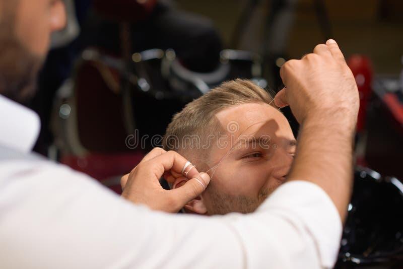 Barbeiro que faz rosqueando o procedimento das sobrancelhas no barbeiro foto de stock royalty free