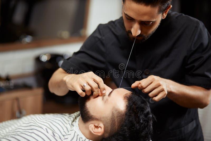 Barbeiro que prepara o homem novo na cadeira foto de stock royalty free